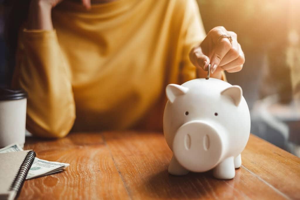 Kvinna lägger ett mynt i en spargris.