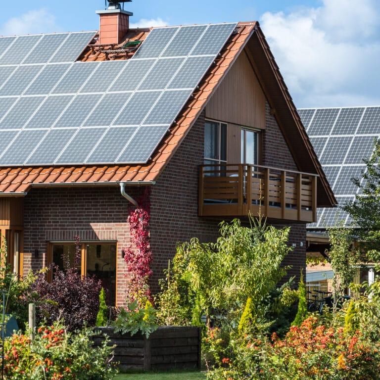 Hus med solpaneler och grön trädgård